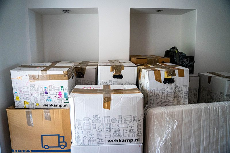 Shifting house. Several stacks of taped-up boxes (branded Ikea and Wehkamp.nl) and a plastic-wrapped mattress imply the owner is in the process of shifting house.