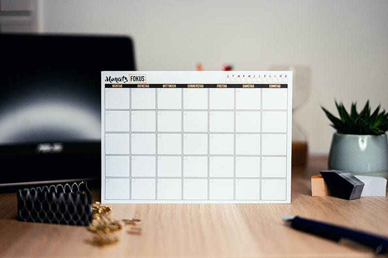 Are you future focused? Bare calendar page with a minimalist background including timber table and cactus plant