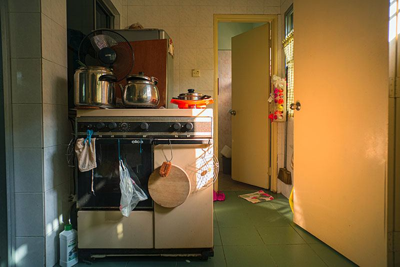 How do I clean my pantry. A messy retro kitchen circa 1960s has a green tiled floor and lemon yellow doors, which open to a further room. Meanwhile pots and a fan sit atop the stove and a teatowel, plastic bag and chopping board dangle from it