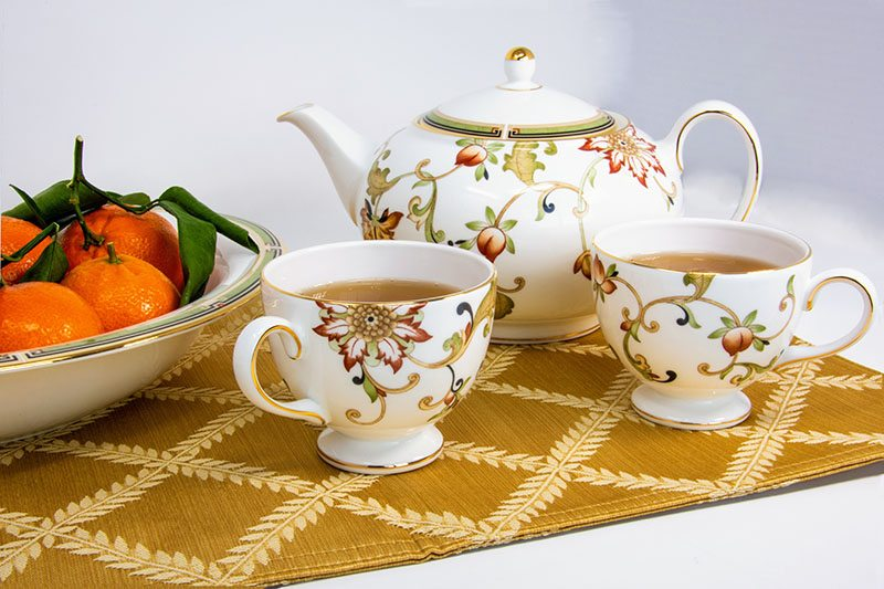 Use the good stuff. Atop a gold leaf-patterned table runner sits a bowl of mandarins, a floral teapot and two floral teacups filled with brown tea