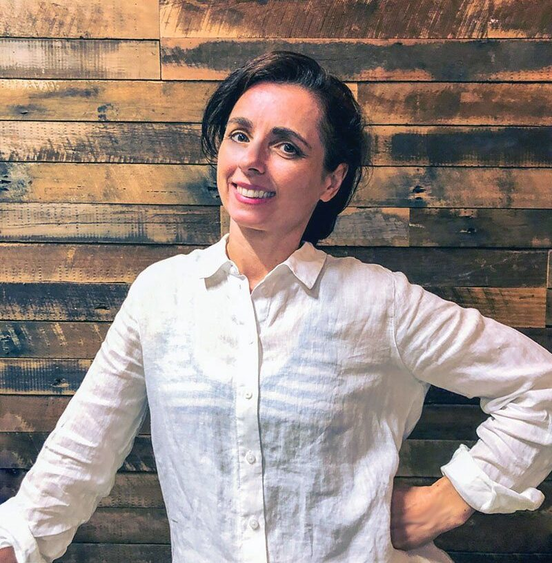 Julie Whiting professional organiser in a white linen shirt in front of a timber wall