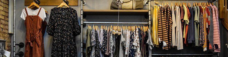 A hanging assortment of dresses and striped tops are arranged neatly. Declutter FAQ