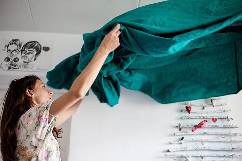 House cleaning on a schedule, as a woman shakes a bedsheet