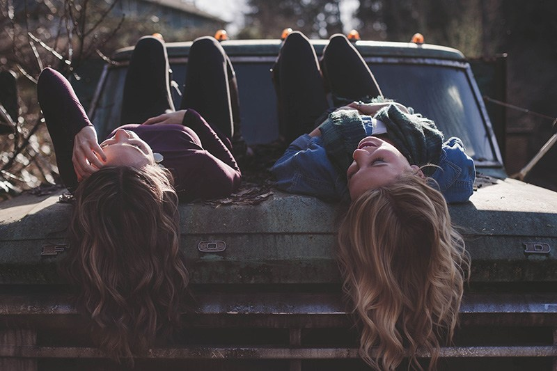 Relationship minimalism and two friends lie on a car to chat